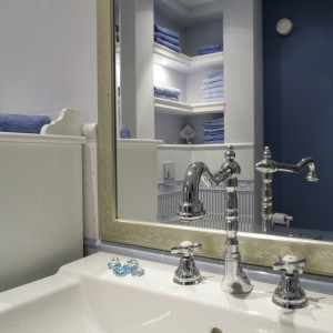Umywalka firmy Duravit została wyposażona w baterię z kolekcji firmy Tres  jednoznacznie kojarząca się ze stylem retro. W ogromnym lustrze przygląda się wnętrze łazienki. Fot. Monika Filipiuk.