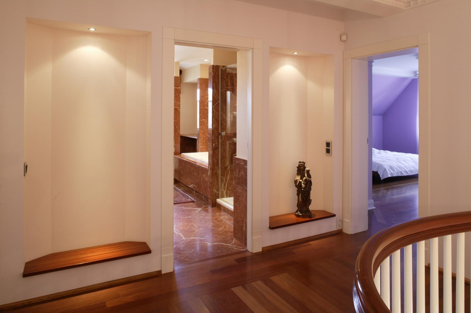 Do łazienki prowadzi wejście z korytarza, ale nierozerwalnie związana jest ze znajdującą się po sąsiedzku sypialnią. Dekoracją holu są podświetlone wnęki. Fot. Bartosz Jarosz.