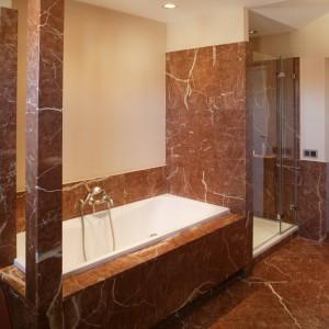 Prostokątna wanna ma efektowną marmurową oprawę ograniczoną z jednej strony ścianą kabiny prysznicowej, z drugiej dekoracyjnymi kolumnami. Fot. Bartosz Jarosz.