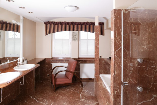 Czerwony marmur pokrywa podłogę i wspina się na ściany. Gdyby nie ten majestatyczny kamień łazienka wydawałaby się całkiem zwyczajna i niemal ascetyczna. Jednak kolor i niezwykła kompozycja żyłkowań czynią z niej wnętrze o charyzmatycznym c