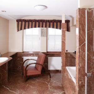 Przedłużony aż do równoległej ściany blat umywalkowy może służyć za toaletkę. Dwa duże okna za dnia doskonale rozświetlają całe wnętrze łazienki. Fot. Bartosz Jarosz.