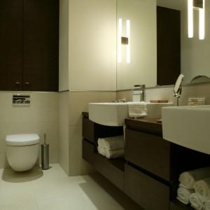 Wnękę nad podtynkowym systemem spłukiwania zabudowano drewnianymi frontami. Na pierwszy rzut oka w łazience są dwie takie szafki – druga to lustrzane odbicie widoczne nad wanną. Fot. Monika Filipiuk.