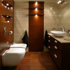 Teatralna gra świateł odkrywa urodę i smaczki łazienki, która jest zarezerwowana dla małżeńskiej sypialni. Połączenie materiałów: dębu barwionego na kolor podłogi (merbau) oraz trawertynu żywicowanego, dało doskonały efekt. Fot. Monika Filipiuk.