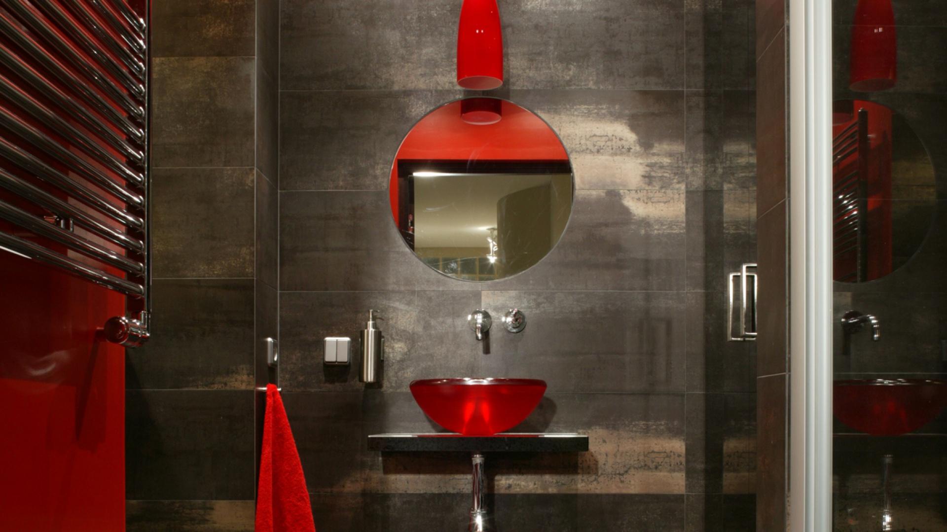 Gościnna toaleta to kwintesencja stylu mieszkania, a zarazem designerski smaczek. Ciemna tonacja wnętrza została ożywiona dokładnie zaplanowanymi detalami w energetycznym kolorze. Mozaikowy czerwony pas biegnący przez podłogę został przeniesiony na sufit. Fot. Monika Filipiuk.
