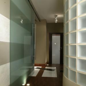 Użyczając łazience metrażu hol niewiele stracił na powierzchni, za to zyskał efektowną, półokrągłą ściankę. Duże, przesuwane drzwi oddzielają hol i kuchnię. Fot. Monika Filipiuk.