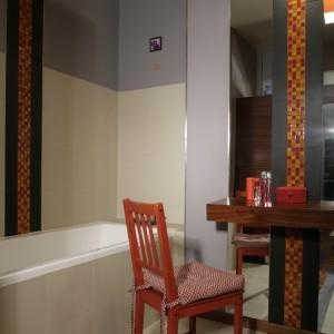 Toaletka wypełnia miejsce naprzeciw wejścia. Z jej lewej strony umieszczono wannę, z prawej szafkę z umywalką. Aluminiowe wykończenie narożnika wzmacnia go, ale też ożywia ciemnoszarą ścianę. Fot. Monika Filipiuk.