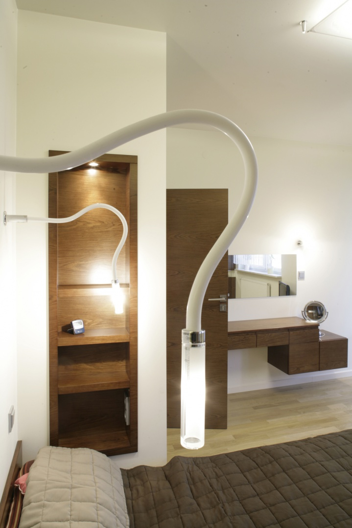 """Małżeńska sypialnia i łazienka są spójne stylistycznie i kolorystycznie. Lampy przy łóżku to jak sam kształt wskazuje model """"Snake"""" włoskiej firmy Fabbian. Fot. Bartosz Jarosz."""