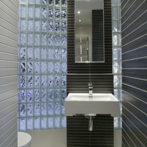 Umywalka i lustro zawieszone zostały na fragmencie ściany między płaszczyznami z pustaków szklanych. Ich niebieskawy kolor ożywia obłożony szarymi płytkami moduł. Fot. Bartosz Jarosz.