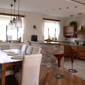 Widok na jadalnię i kuchnię od strony salonu. Strefę jadalniano-kuchenną symbolicznie oddziela od salonu bejcowania belka sufitowa z drewna szczotkowanego oraz pas podwieszanego sufitu. Fot. Monika Filipiuk.