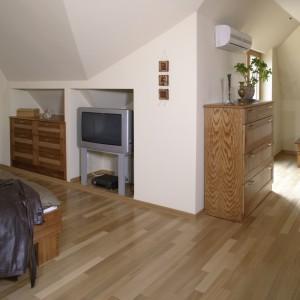 Za sprawą dużej ilości drewna, sypialnia jest bardzo przytulna. Na podłodze ułożono parkiet jatoba, a wszystkie meble wykonane są z dębu, barwionego na złoty orzech. Fot. Monika Filipiuk.