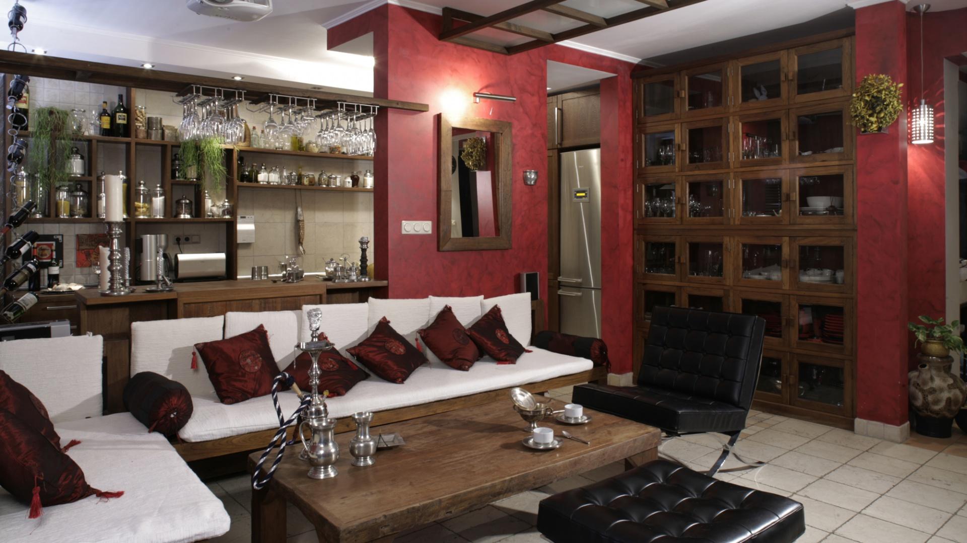 Zaskakujący, designerski akcent pojawia się w części wypoczynkowej salonu. Replika oryginalnego fotela Barcelona, zaprojektowanego przez Ludwiga Miesa van der Rohe, w ciekawy sposób przełamuje wszechobecny, orientalny styl wnętrza. Fot. Monika Filipiuk.