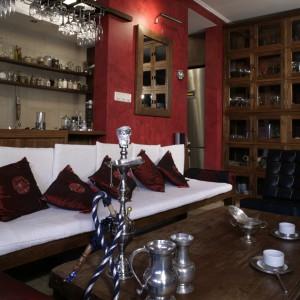 Imponujący, wysoki kredens, umieszczony tuż przy wejściu do kuchni, wspaniale eksponuje kolekcję szkła i porcelany. Kredens, którego front został stworzony z 12 par kwadratowych, oszklonych drzwiczek, nieprzypadkowo przypomina chiński parawan. Fot. Monika Filipiuk.