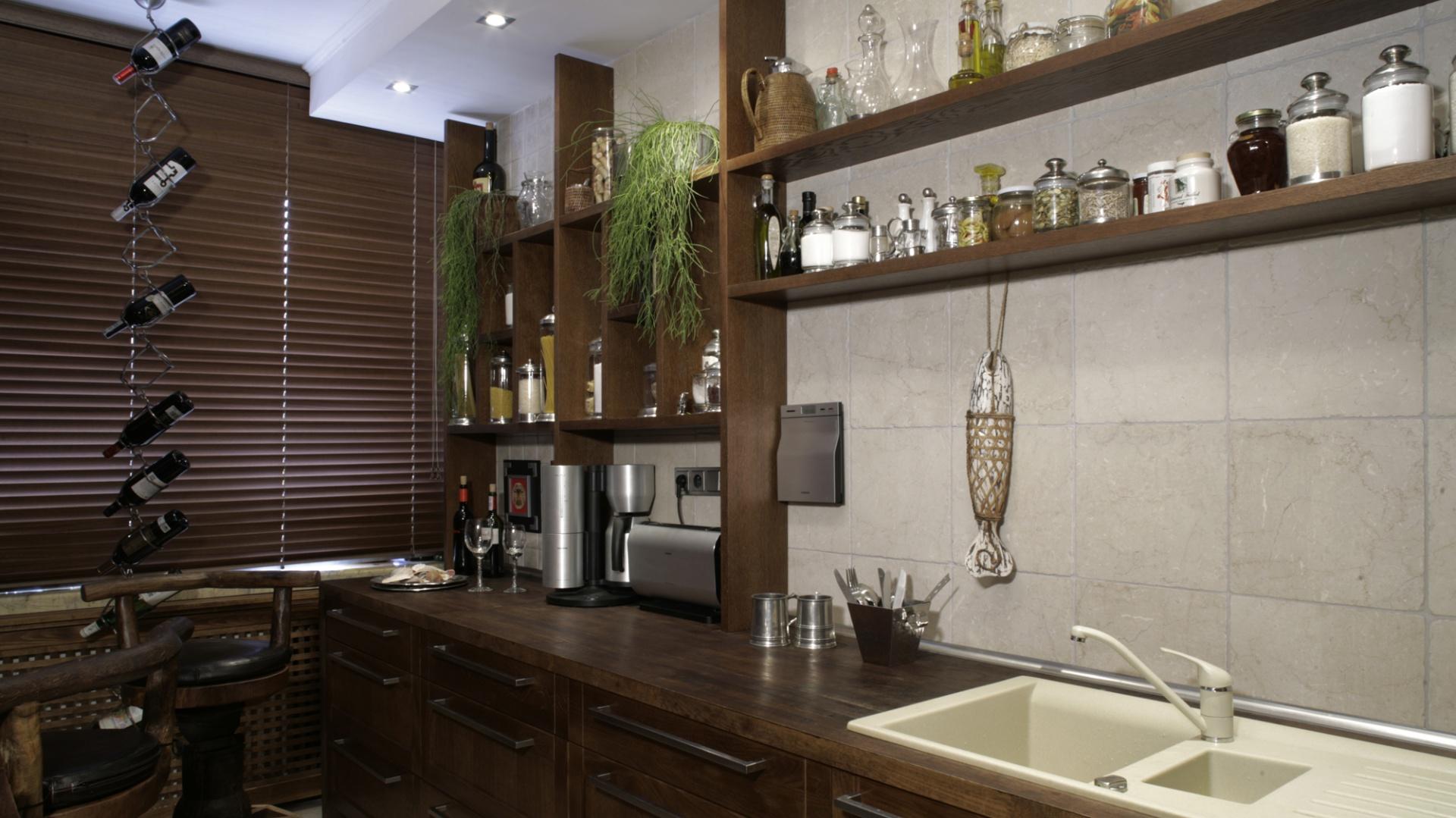 """""""Regał"""" na kuchennej ścianie został stworzony z drewnianych podziałów, których wzór zaczerpnięto z oparć jadalnianych krzeseł (kolejne nawiązanie do chińskich parawanów). Oryginalne i stylowe chińskie hokery, będące połączeniem naturalnego drewna i skóry. Fot. Monika Filipiuk."""