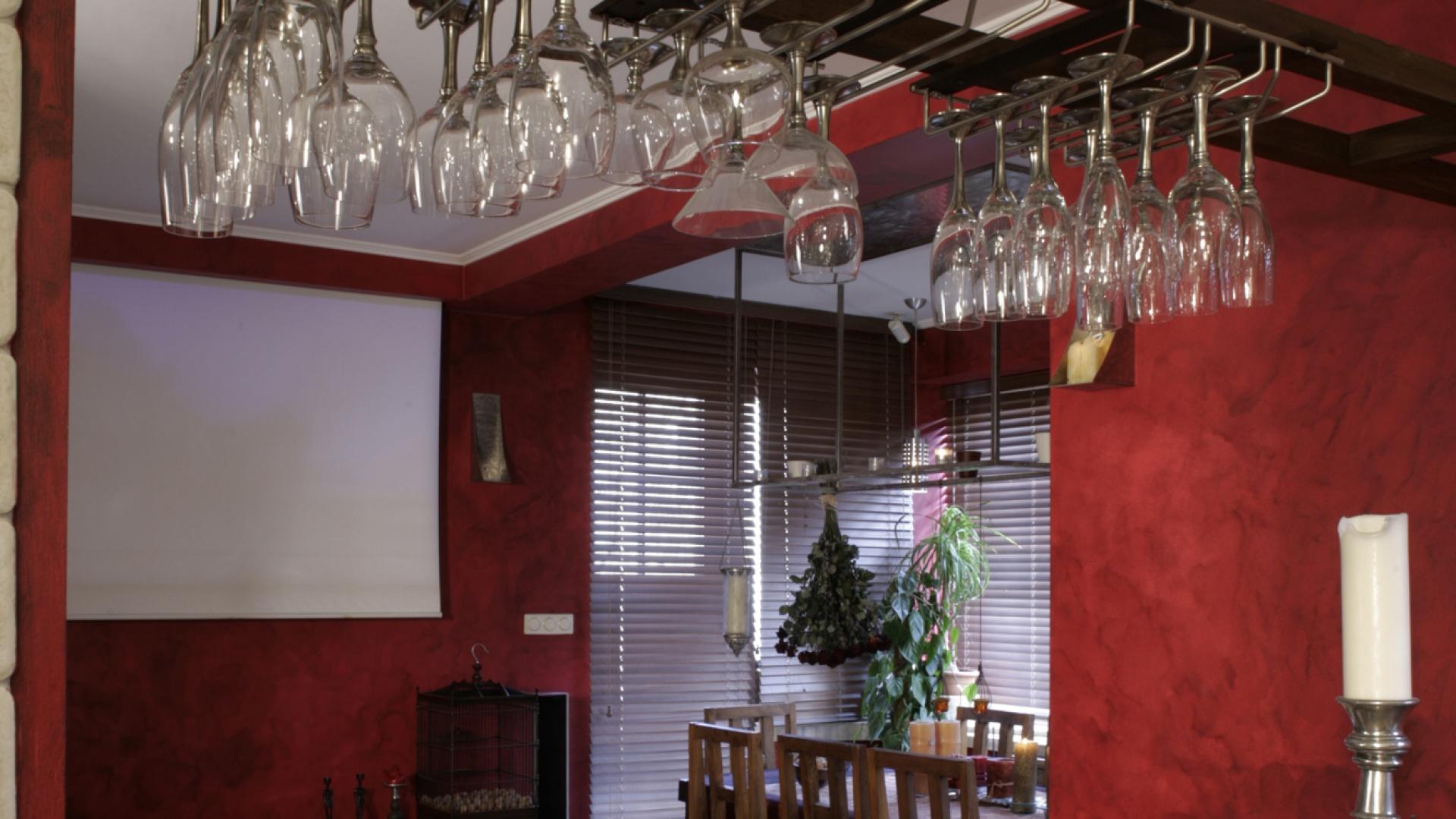 Z umieszczonego pod kuchennym sufitem rzutnika, na wysuwanym w salonie ekranie, wyświetlane są filmy i zdjęcia z podróży gospodarza. Nad barem efektownie zwisają prawdziwe cacka – piękna kolekcja kieliszków z nóżkami wykonanymi ze srebra. Fot. Monika Filipiuk.