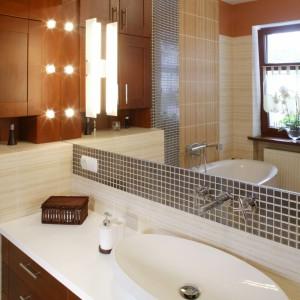 Ogromne lustro nad umywalką dodaje wizualnej przestrzeni. Ściana nad nim, podobnie jak przeciwległa, pomalowano na ciepły ceglany kolor. Fot. Monika Filipiuk.