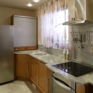 Właściciele domu bardzo nie lubią widoku kuchennego rozgardiaszu, stąd wszystkie szafki mają wypełnione drewnem, nieprzezroczyste fronty. Obok lodówki widać półkę z wygodną w obsłudze roletą. Fot. Monika Filipiuk.
