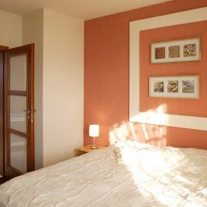 Ciepła i jasna kolorystyka sypialni płynnie przechodzi do łazienkowego wnętrza. Kompozycja obrazków nad łóżkiem to znak, że w tym domu królują naturalne barwy i materiały. Fot. Monika Filipiuk.