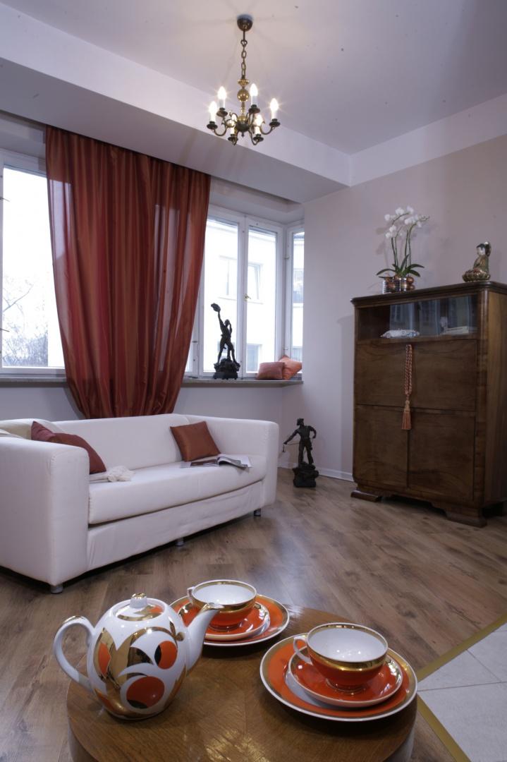Wnętrze salonu, urządzone z niezwykłą swobodą, dzięki zastosowanej kolorystyce jest również bardzo konsekwentne. Zasłony w kolorze rozgrzanej pomarańczy bardziej zdobią, niż przesłaniają okno. Fot. Monika Filipiuk.