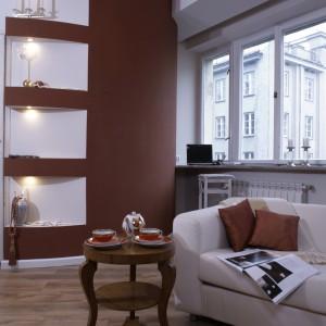 Półokrągła ściana, w intensywnym czerwono-pomarańczowym kolorze, wyodrębniła z otwartej przestrzeni sypialnię właścicieli. W zaprojektowanych w ścianie podświetlanych niszach wyeksponowano kilka dekoracyjnych bibelotów. Fot. Monika Filipiuk.
