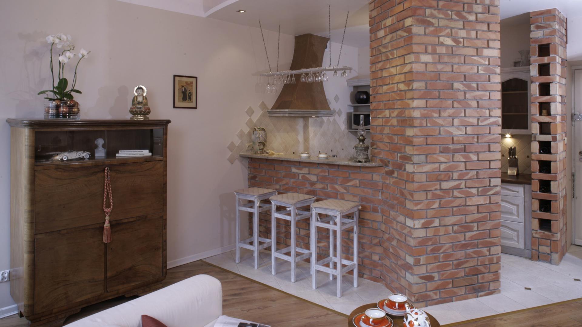 Konstrukcja z czerwonej, palonej cegły, wybudowana przy wejściu do kuchni, skrywa w sobie lodówkę. Po przeciwnej stronie powstało kilka wnęk, które gospodarze wykorzystali jako leżak na wino. Fot. Monika Filipiuk.