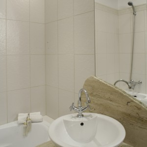 Okrągły kształt blatu pod umywalką, nachodzącego lekko na wannę, podyktowały niewielkie rozmiary łazienki. Kamienna płyta (surowy trawertyn), nałożona częściowo na lustro, stała się również ciekawą ozdobą ściany. Fot. Monika Filipiuk.