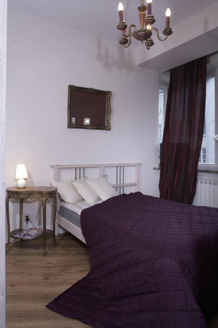 Tuż przy łóżku gospodyni ustawiła wiekową konsolkę, pełniącą rolę nocnego stolika. Intarsjowany mebelek, pochodzący z przełomu XIX i XX wieku, to kolejny stylowy akcent we wnętrzu. Łóżko przykrywa pikowana narzuta w kolorze dojrzałej śliwki węgierki. Fot. Monika Filipiuk.