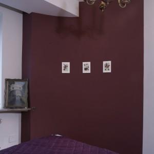 Wklęsła, półokrągła ściana w sypialni została pomalowana na bordowo. Zdobią ją trzy małe obrazki, powielające motyw kolorystyczny tła. Na parapecie pastel w postarzanych ramach, przedstawiający widok z Wenecji. Fot. Monika Filipiuk.
