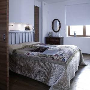 Ogromne łóżko na stalowych ramach to jedyny nowoczesny mebel w sypialni gospodarzy. Jego wezgłowie zdobi podświetlana nisza, gdzie gospodarze trzymają głównie książki, które czytają przed snem. Fot. Monika Filipiuk.