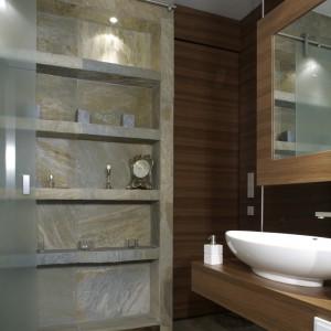 Półki na całej długości ściany wraz z osłaniającymi je frontami z matowego szkła są tyleż użyteczne, co dekoracyjne. Podobnie jak większość ścian pokrywają je płytki imitujące kamień łupek. Fot. Monika Filipiuk.
