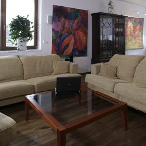 Wypoczynek oraz szklany stolik przywędrował tu, jak większość mebli, z poprzedniego lokum właścicieli. Ogromne, niezwykle barwne obrazy, zdobiące niemal każdy kąt apartamentu, znalazły się tu na specjalne życzenie gospodarzy. Fot. Monika Filipiuk.