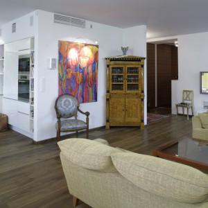 Stylowy kredens oraz krzesło w klasycznym stylu, znakomicie prezentują się w nowoczesnej otoczce. Urody temu miejscu dodaje odważny zabieg aranżacyjny – wielkoformatowe płótno, zdobiące ścianę w salonie. Fot. Monika Filipiuk.