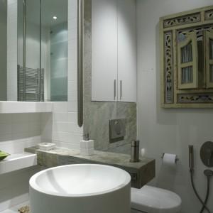 """Ascezę wnętrza gościnnej łazienki przełamuje nietypowa ozdoba – lustro w indyjskiej ramie, przesłonięte dekoracyjnymi """"okiennicami"""". W egzotycznym stylu jest również pojemnik na chusteczki, udekorowany maleńkimi chwostami i ustawiony na półce pod lustrem. Fot. Monika Filipiuk."""
