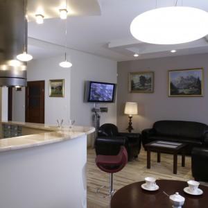 Nowoczesny, kamienny stół-blat oświetlają trzy zwisające lampy, wspomagane przez wprawione w podwieszany sufit lampeczki halogenowe. Zawieszony na ścianie telewizor podświetla klasyczna, stojąca lampa. Fot. Monika Filipiuk.