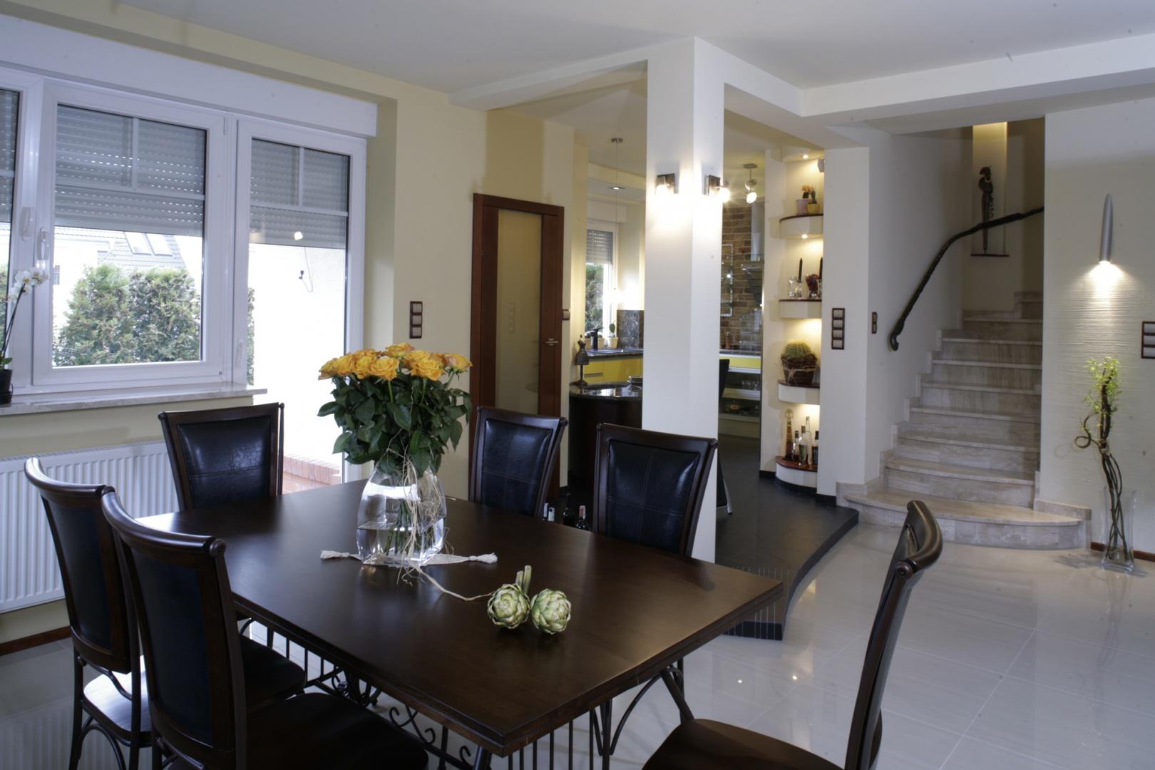 Drewniany stół jadalniany na kutych z metalu nogach i obite skórą krzesła nawiązują do stylistyki retro. A jednak stanowią część tego nowoczesnego domu. Fot. Monika Filipiuk.