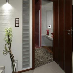 Po otwarciu drzwi od razu widać, że łazienka dzieli się na dwie kontrastujące strefy. Falista linia na podłodze, przypominająca chiński symbol Yin Yang sugeruje, że przeciwieństwa się tu wzajemnie warunkują i dopełniają.