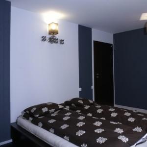 Oprócz lamp, dekoracyjną rolę pełni także ozdobna, niebieska tapeta, specjalnie wybrana przez panią domu. Za wytapetowaną ścianą znajduje się garderoba, dlatego ilość mebli w sypialni została ograniczona do minimum. Fot. Monika Filipiuk.