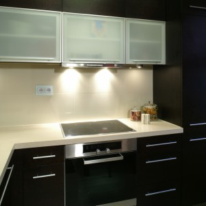 Meble kuchennej zabudowy zostały wykonane na zamówienie przez włoską firmę Scavolini. Ich elegancki, mocny kolor to efekt zastosowania bardzo ciemnego forniru wenge. Fot. Bartosz Jarosz.