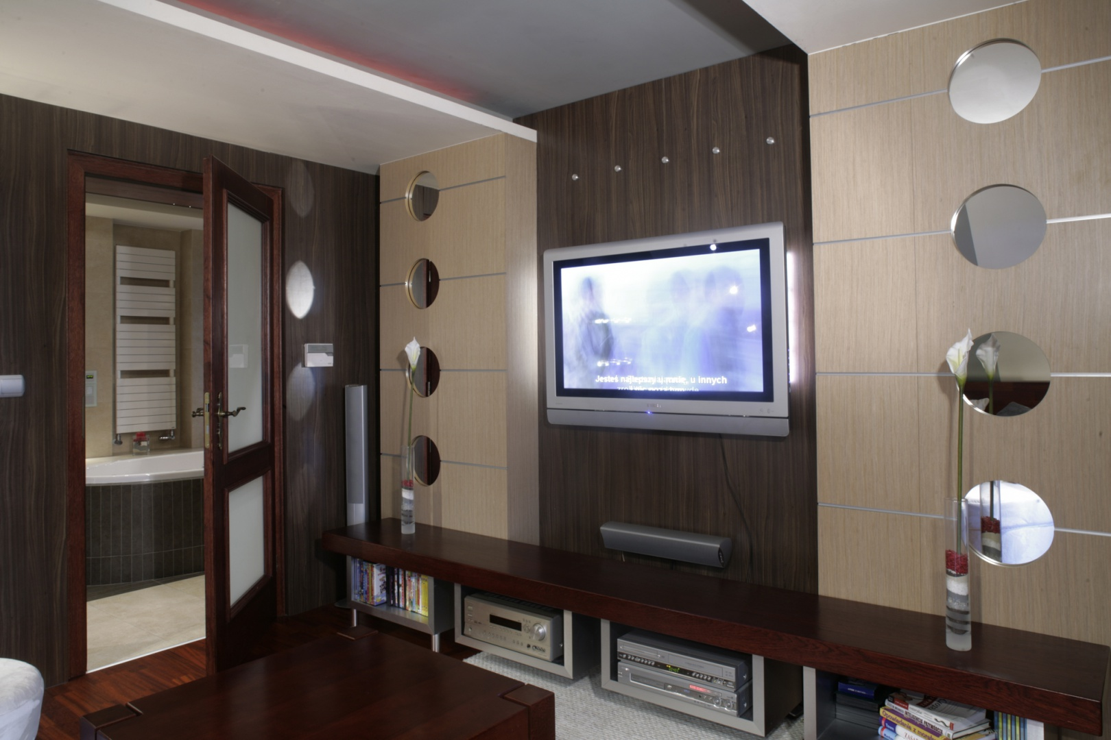 """Jedno z wejść do łazienki prowadzi z pokoju telewizyjnego, który sąsiaduje z małżeńską sypialnią. Ściana z laminatu, o przypominającej drewno fakturze, jest elementem wywołującym efekt """"ciepłej nowoczesności"""" tego domu. Fot. Monika Filipiuk."""