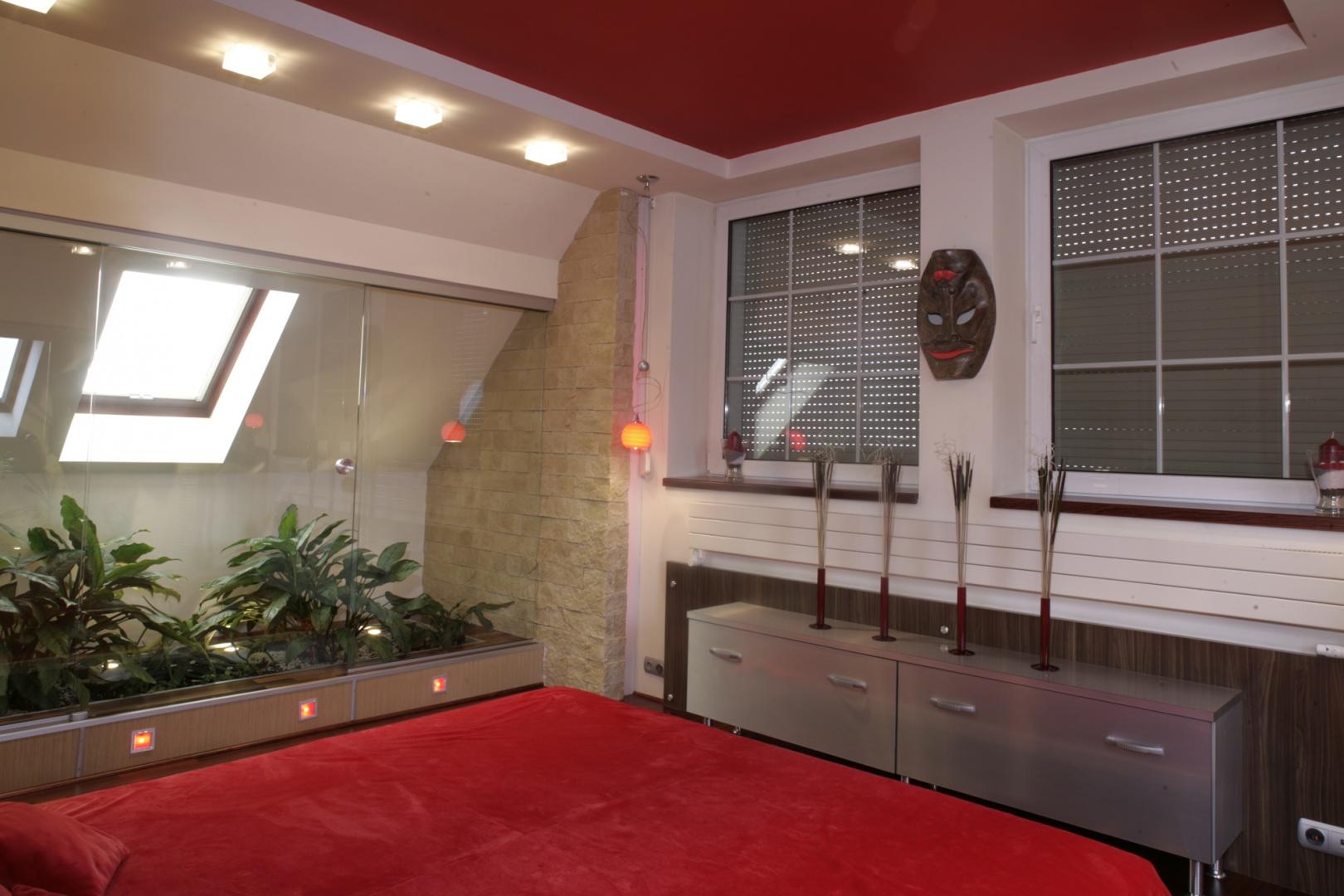 Srebrna komoda z laminatu (Abet Laminati), pokryte drewnem elementy ścian, wreszcie efektowna oszklona oranżeria – zajmująca niemal połowę sypialni. Fot. Monika Filipiuk.
