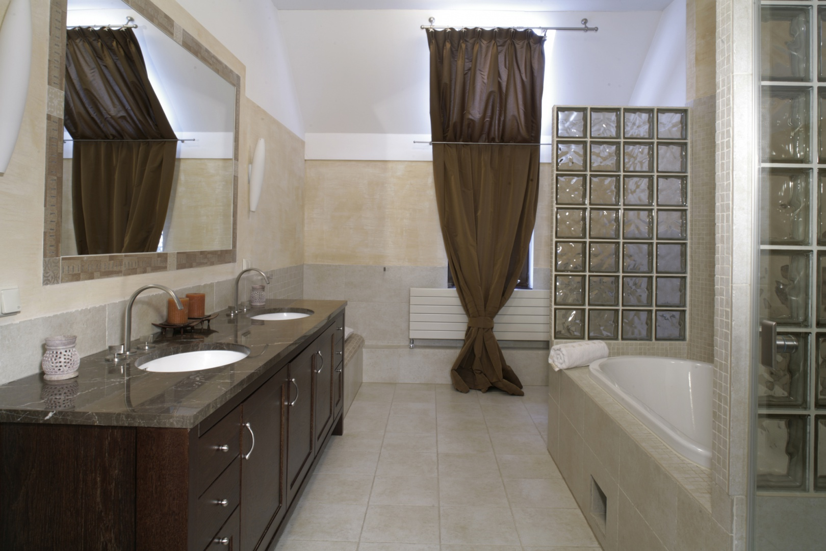 Dwie umywalki to standard w małżeńskiej łazience. Niezwykle elegancko prezentują się podwieszone pod marmurowym blatem na drewnianej komodzie. Fot. Monika Filipiuk.