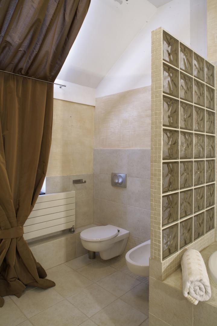 Sedes i bidet ulokowane zostały w najmniej widocznym miejscu – w narożniku łazienki, za wyodrębniającą wannę ścianką z pustaków szklanych. Fot. Monika Filipiuk.