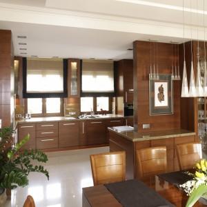 Wnętrze jest przestronne i jasne. Światło dzienne zapewniają duże okna. Po zapadnięciu zmroku kuchnię rozświetlają rzędy halogenów wzdłuż zabudowy, jadalnię – lampa nad stołem i światło ukryte w podwieszanym suficie. Fot. Bartosz Jarosz.