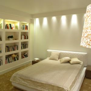Łóżko z pikowanym zagłówkiem to wytworny akcent nowoczesnej i minimalistycznej sypialni. Mebel wyeksponowany został za pomocą światła, które wydobywa się z ukrytych w sufitowym gzymsie halogenów. Fot. Monika Filipiuk.