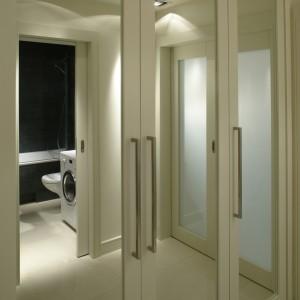 Wśród jasnych wnętrz w tym mieszkaniu grafitowa kolorystyka łazienki jest zaskoczeniem. Od holu oddzielona została przesuwnymi drzwiami z dużą wstawką z matowego szkła. Fot. Bartosz Jarosz.