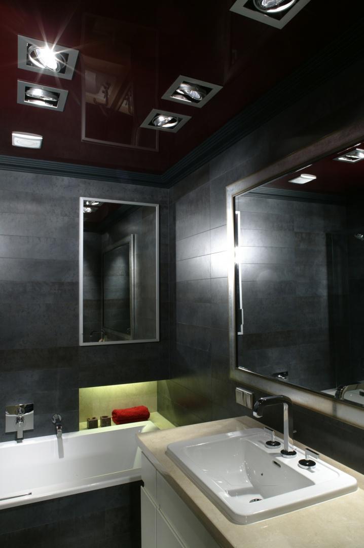 W lśniącej tafli napinanego sufitu w głębokim kolorze wina odbija się całe wnętrze łazienki. Rozświetlają go halogeny w wydatnych, nowoczesnych oprawach. Fot. Bartosz Jarosz.