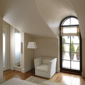 Prosto z gościnnego pokoju można dostać się na taras, wyjściem zwieńczonym półokrągłym sklepieniem. Jeden z kątów sypialni zajmuje szafa ubraniowa z frontem przykrytym pionową taflą lustra. Fot. Bartosz Jarosz.