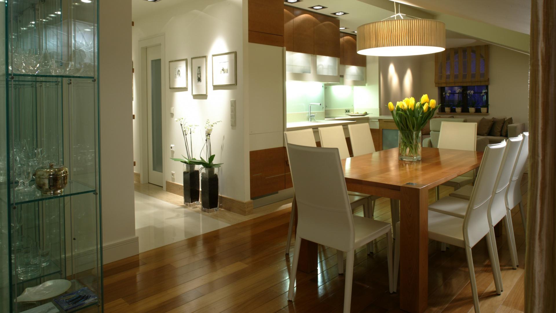 Jadalnia, kuchnia i salon tworzą jedną, otwarta przestrzeń. W centrum postawiono czereśniowy stół otoczony kompletem krzeseł w skórzanej tapicerce. Większość frontów zabudowy kuchennej wykonano z lakierowanego mdf-u (orzech barwiony). Fot. Bartosz Jarosz.
