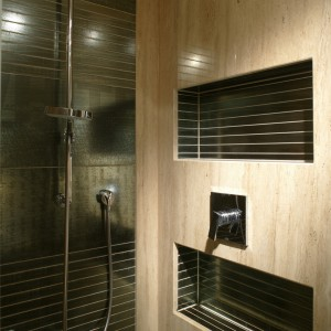 Wnętrze kabiny prysznicowej w gościnnym WC wyłożono trawertynem i płytkami o ciemnostalowej barwie (Irys). Fot. Bartosz Jarosz.
