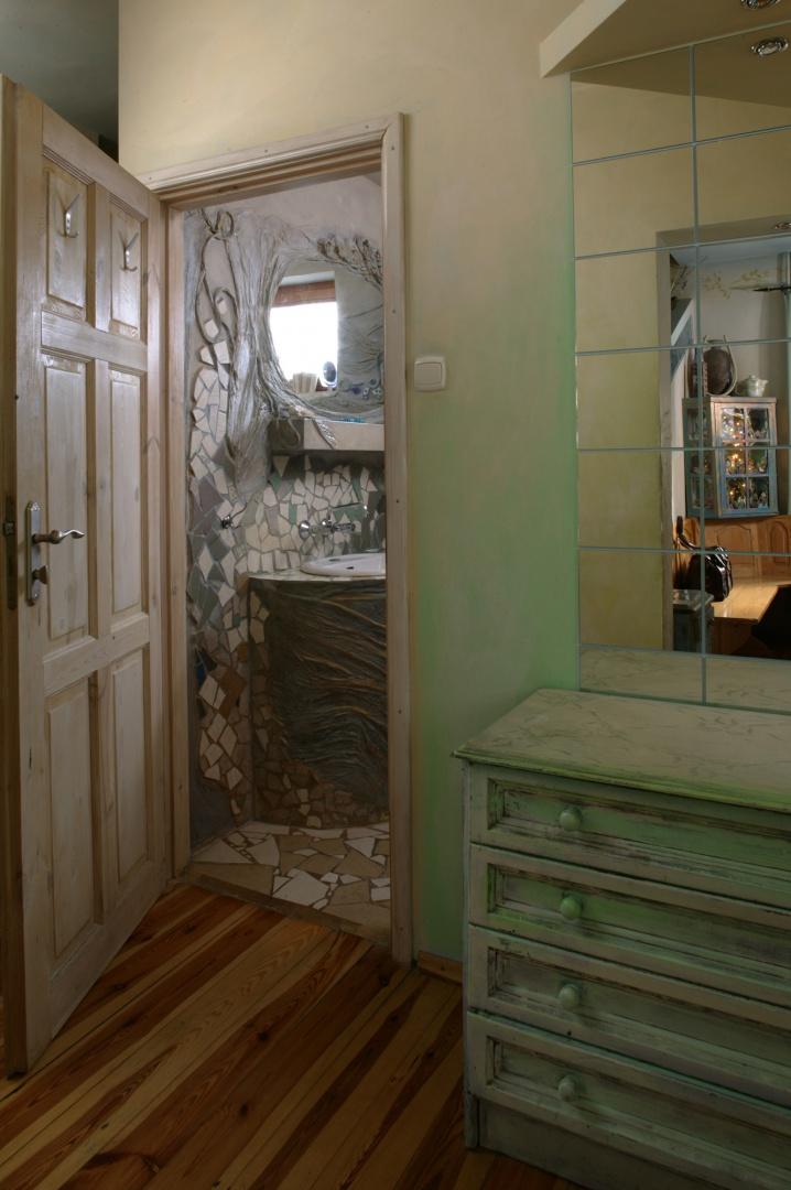 Drzwi do łazienki prowadzą z korytarza, którego umeblowanie to również efekt pracy właścicielki mieszkania. Prosta, sosnowa podłoga świetnie współgra z bajkowymi sprzętami. Fot. Bartosz Jarosz.