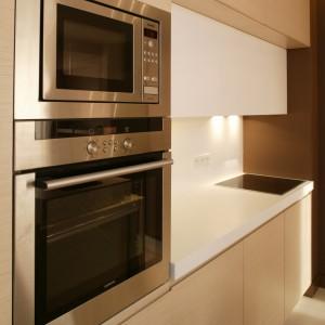 Kuchenna zabudowa mieści nie tylko piekarnik i kuchenkę mikrofalową, ale też, ukrytą za jednym z frontów szafek, pralkę. Fot. Bartosz Jarosz
